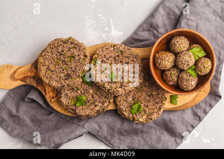 Vegan beans burgers (cutlets) and meatballs with parsley on a wooden board, copy space. Healthy vegan food concept. - Stock Photo
