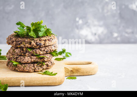 Vegan beans burgers (cutlets) with parsley on a wooden board.  Healthy vegan food concept. - Stock Photo