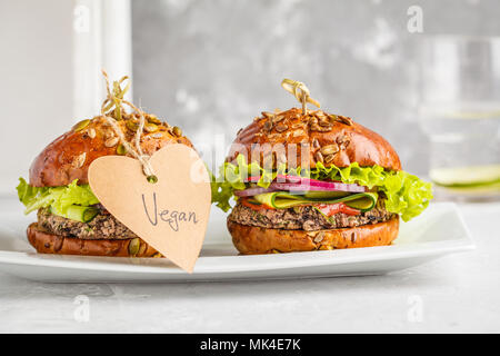Vegan bean burgers with vegetables and tomato sauce on white dish, copy space. Healthy vegan food concept. - Stock Photo
