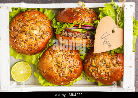 Vegan bean burger with vegetables and tomato sauce in white wooden box, top view. Healthy vegan food concept. - Stock Photo