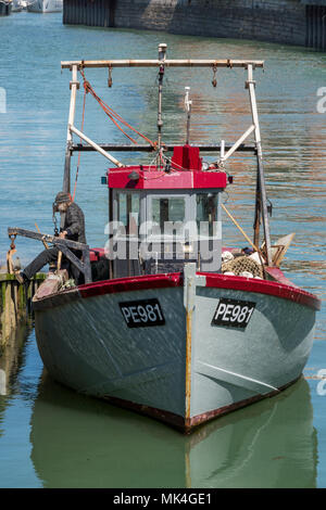 a small fishing trawler or boat with a fisherman on the deck in the fishing quay at portsmouth harbour. fishing and commercial boats on south coast. - Stock Photo