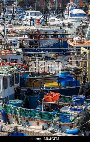 fishing boats packed into the harbour at portsmouth fishing fishermans quay in the port. colourfyl tangle of boats ropes and nets jumbled and chaotic. - Stock Photo