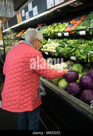 An elderly, gray-haired woman in a pink coat shopping for cabbage in the fresh produce section in a market. - Stock Photo