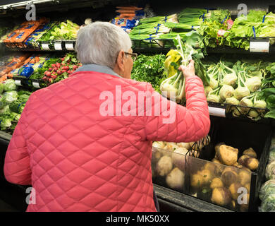 An elderly, gray-haired woman in a pink coat shopping for kohlrabi in the produce section of a market. - Stock Photo
