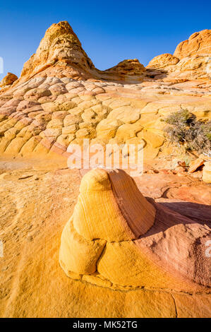 Sandstone rock with different color stripes rests on Sandstone formation showing same stripe South Coyote Buttes Vermilion Cliffs National Monument - Stock Photo