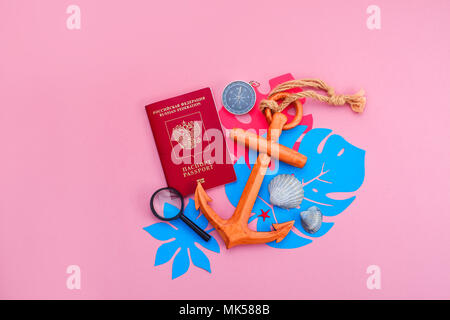 Colorful travel and vacation concept on a bright pink background. Tropical leaves, wooden anchor, passport, compass and seashells with copy space. - Stock Photo