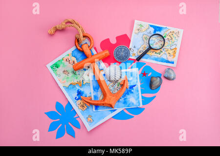 Tropical leaves, wooden anchor, magnifying glass, watercolor maps, compass and seashells with copy space. Colorful travel and vacation concept on a bright pink background. - Stock Photo