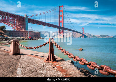 Classic view of famous Golden Gate Bridge with Fort Point National Historic Site on a beautiful sunny day with blue sky and clouds, San Francisco, USA - Stock Photo