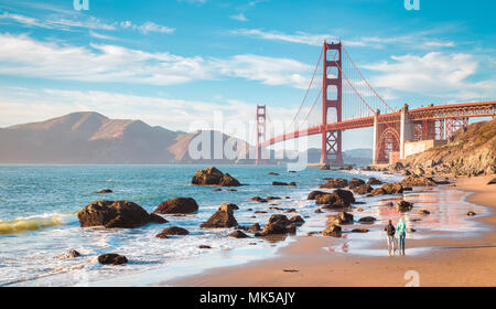 Classic panoramic view of famous Golden Gate Bridge seen from scenic Baker Beach in beautiful golden evening light on a sunny day with blue sky and cl - Stock Photo