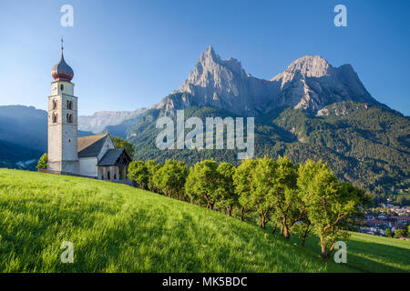 Idyllic mountain scenery in the Dolomites with St. Valentin Church and famous Mount Sciliar in beautiful morning light at sunrise, South Tyrol, Italy - Stock Photo