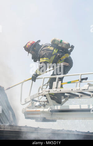 A firefighter stands on a truck ladder over a roof wiht a tool. He is taking apart a smoldering roof to look for hot spots to put out. - Stock Photo
