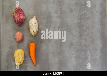 Great concept of healthy food, various vegetables, potatoes, sweet potatoes, carrots, on gray background, polished concrete. - Stock Photo