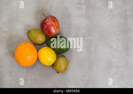 Great concept of healthy eating, various fruits on gray background, polished concrete. Orange, apple, kiwi, lemon. - Stock Photo