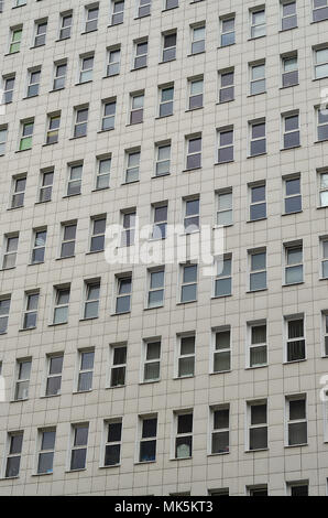 A pattern of many windows from a multi-storey office building. A large number of plastic windows in the wall of a modern multi-storey building - Stock Photo