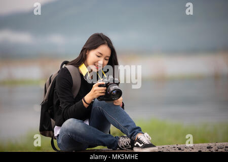sian  young women people Hiking with friends backpacks walking together and looking map and taking photo camera by the road and looking happy ,Relax t - Stock Photo