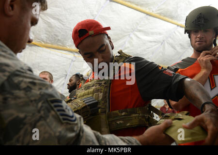 U.S. Air Force Tech. Sgt. Brian Jones, assistant security forces flight chief for U.S. Special Operations Command Deployment Cell, helps Tampa Bay Buccaneers wide receiver DeSean Jackson and third-string quarterback Ryan Griffin try on tactical gear during their visit to MacDill Air Force Base in Tampa, Fla., Nov. 7, 2017. The football players and cheerleaders toured USSOCOM and other base facilities to meet with currently serving personnel and to experience a glimpse of military life. (Photo by U.S. Air Force Master Sgt. Barry Loo) - Stock Photo