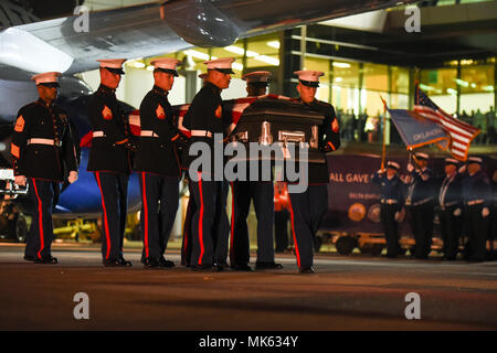 A Marine Corps carry team transfers the remains of Marine Pvt. Vernon Paul Keaton November 14, 2017, Will Rogers World Airport, Oklahoma City, Oklahoma. Keaton was killed Dec. 7, 1941, during the Japanese attack on Pearl Harbor, Hawaii. Marines from Rocket Battery F, 2nd Battalion, 14th Marine Regiment, 4th Marine Division, based at the Marine Corps Reserve Center in Oklahoma City provided the carry team and honors and were joined by a flag detail from the Department of Homeland Security/Transportation Security Administration shown in the background. (U.S. Air Force photo/Greg L. Davis) - Stock Photo