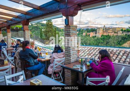Granada, Spain: Tourists at El Balcón de San Nicolás cafe and restaurant in the Albaicin district old town, enjoy a panoramic view of the Unesco liste - Stock Photo