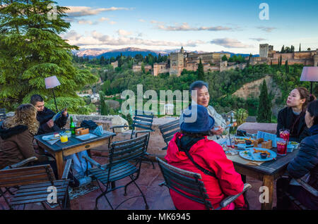 Granada, Andalusia, Spain - April 29th, 2018 : Tourists at Huerto de Juan Ranas cafe and restaurant in the Albaicin district old town, enjoy a panoram - Stock Photo