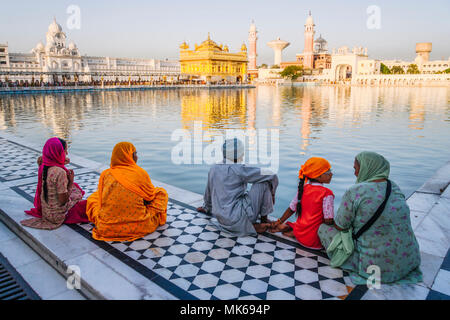 Amritsar, Punjab, India : A Sikh family sits by the pool in the Golden Temple. - Stock Photo