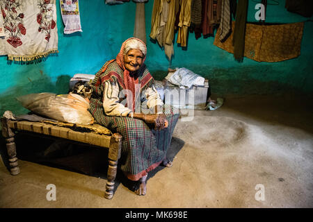 Old Indian woman sitting on a charpoy bed at her house in Naggar, Himachal Pradesh, India - Stock Photo
