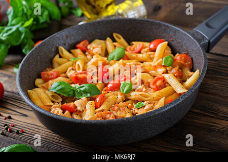 Penne pasta in tomato sauce with chicken, tomatoes, decorated with basil on a wooden table. Italian food. Pasta Bolognese. - Stock Photo