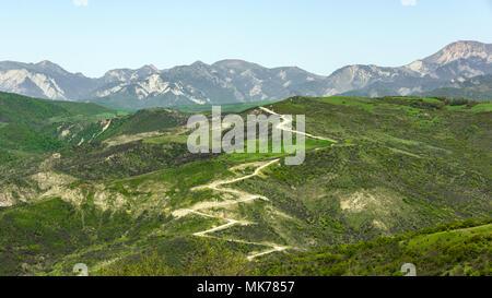 A winding mountain dirt road - Stock Photo