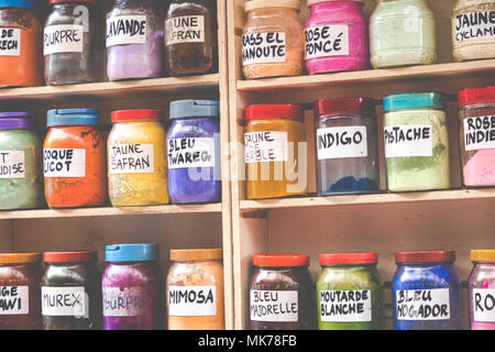 Assortment of glass jars on shelves in herbalist shop on a traditional Moroccan market (souk) in Marrakech, Morocco - Stock Photo