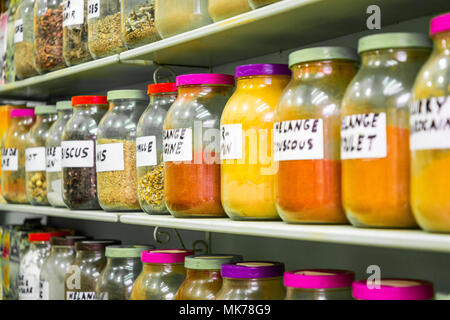 Assortment of glass jars on shelves in herbalist shop on a traditional Moroccan market (souk) in Essaouira, Morocco - Stock Photo