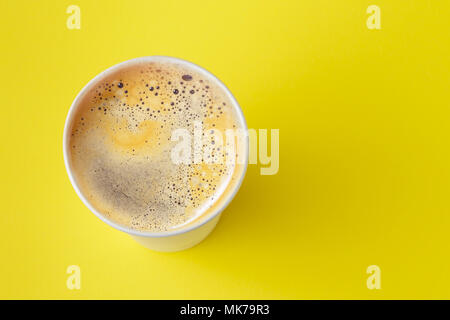 Top view of take-out hot drink in opened thermo cup on vibrant yellow background. Cafe crema foam on the americano coffee - Stock Photo