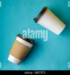 Take away coffee drink in disposable paper cup over turquoise wooden background - Stock Photo