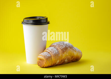 Take away coffee drink with croissant on yellow background - Stock Photo