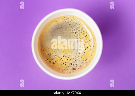 Top view of take-out hot drink in opened thermo cup on vibrant purple background. Cafe crema foam on the americano coffee - Stock Photo