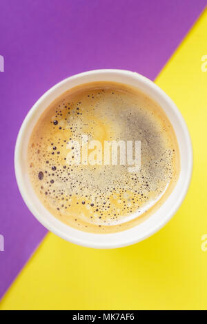 Top view of take-out hot drink in opened thermo cup on vibrant purple and yellow background. Cafe crema foam on the americano coffee - Stock Photo