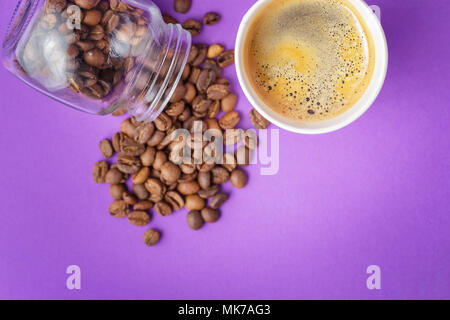 Top view of take-out hot drink in opened thermo cup and coffee beans scattered from glass jar on vibrant purple background. Cafe crema foam on the ame - Stock Photo