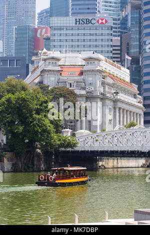For tourist destination in Singapore, ride a bumboat for a river cruise along Singapore river, able to check out the Fullerton Hotel built in 1919. - Stock Photo