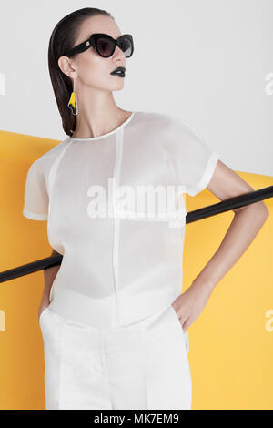 Emotionless young model in trendy white costume wearing black lipstick and sunglasses standing with black stick on colorful background. - Stock Photo