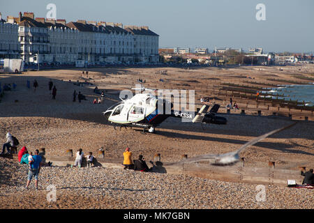 Eastbourne Sussex UK May 5th 2018: Air Ambulance lands on Eastbourne seafront with sunbathers onlooking - Stock Photo