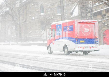 Hamilton, Ontario, Canada - February 2013: A Canada Post Delivery truck try to make deliveries during severe snowfall - Stock Photo