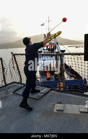 171114-N-QR145-055  NAVAL SUPPORT ACTIVITY SOUDA BAY, Greece (Nov. 14, 2017)   Electronics Technician 2nd Class Manuel Bolanos throws a heaving line to a tugboat as the Arleigh Burke-class guided-missile destroyer USS Porter (DDG 78) departs Naval Support Activity Souda Bay, Greece, Nov. 14, 2017. Porter, forward-deployed to Rota, Spain, is on its fourth patrol in the U.S. 6th Fleet area of operations in support of regional allies and partners, and U.S. national security interests in Europe. (U.S. Navy photo by Mass Communication Specialist 3rd Class Krystina Coffey/ Released) - Stock Photo