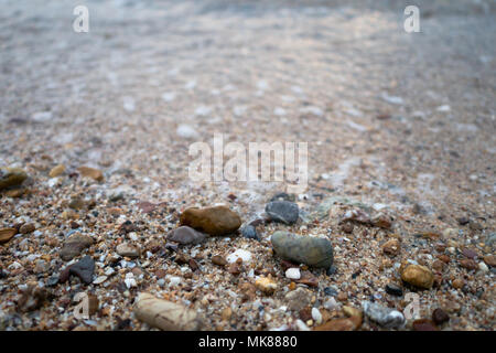 Sea waves on the beach with full of stones, use for background. Select focus shallow depth of field - Stock Photo