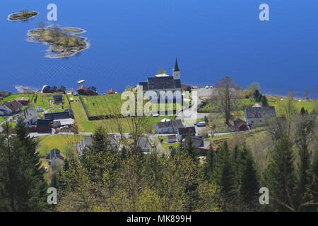 View over the small village of Bruvik on the island of Osterøy in Hordaland, Norway, on April 20, 2014. Bruvik church and cemetery is in view. - Stock Photo