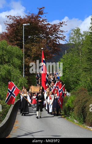 Patriotic Norwegian men and women carry the country flag during a national day parade on 17 May in the town of Vaksdal, in Hordaland County, Norway. - Stock Photo