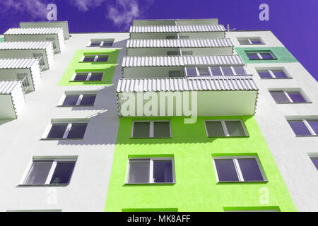 View from below upwards on blue sky and multi-storey house - Stock Photo