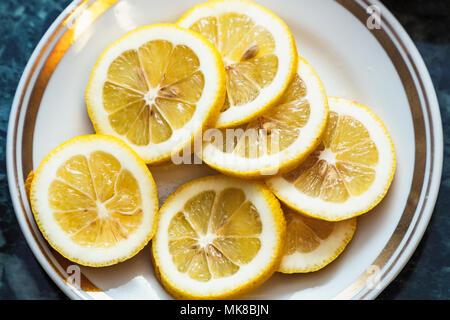 Slices of lemon on white plate - Stock Photo