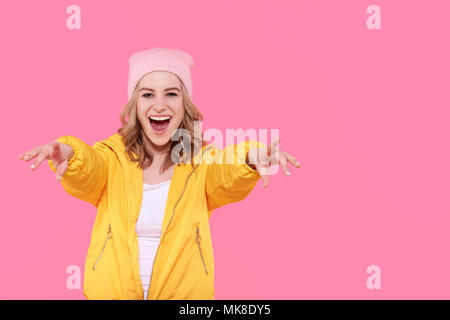 Beautiful hipster teenage girl in bright yellow jacket and pink beanie hat super excited. Attractive cool young woman fashion portrait over pastel pin - Stock Photo