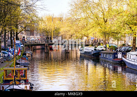 View on beautiful Amsterdam, capital of the Netherlands, with canals, canalboats, trees and reflections in the water - Stock Photo