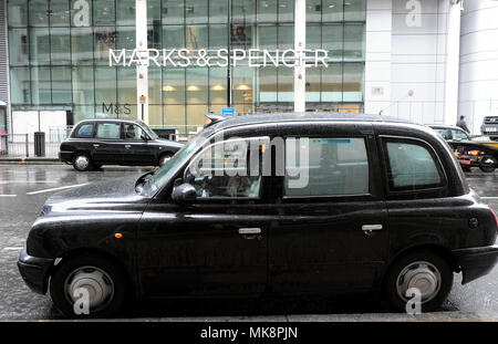 Taxi parked outside Marks & Spencer store in Moorgate on a rainy day in spring in the City of London UK  KATHY DEWITT - Stock Photo