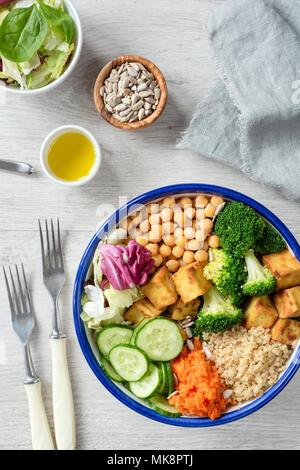 Colorful buddha bowl, healthy vegetarian salad. Buddha bowl with sweet potato, quinoa, chickpeas, broccoli, baked tofu, cucumber and green salad leaf. - Stock Photo