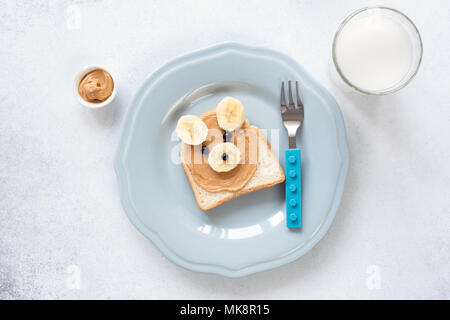 Peanut butter and banana toast shaped as bear, breakfast or lunch for kids. Food art. Healthy food for kids. Animal food art. Fun with food - Stock Photo